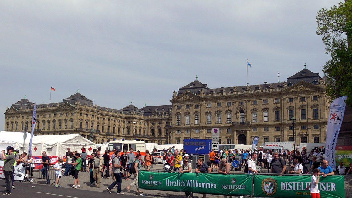 Резиденция Вюрцбурга. Резиденция епископа. На большой площади перед зданием шумит городская ярмарка, под громкие крики стартуют участники популярного спортивного соревнования «Decatlon» (десятиборье).