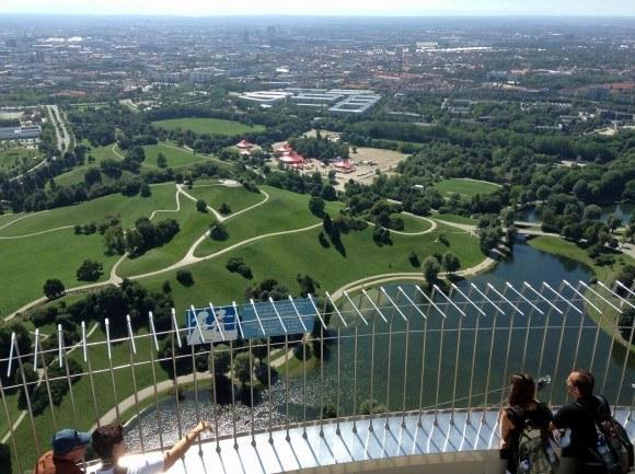 Олимпийская башня Мюнхена. Панорама Олимпийской горы и города с высоты верхней платформы. На первом плане видно ограждение нижней открытой платформы.