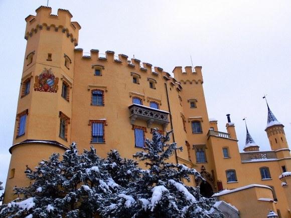Замок Хоэншвангау. Башни, балконы, гербы на стенах замка, построенного в английском стиле тюдор.